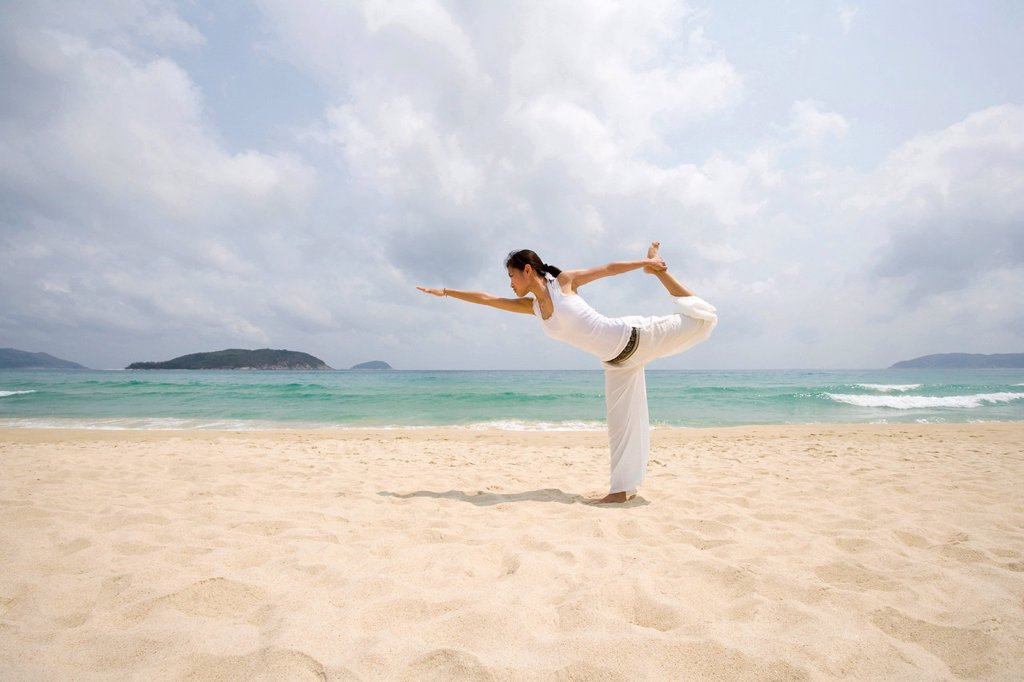 Stock Photo: 1839R-18373 Young woman doing yoga on the beach