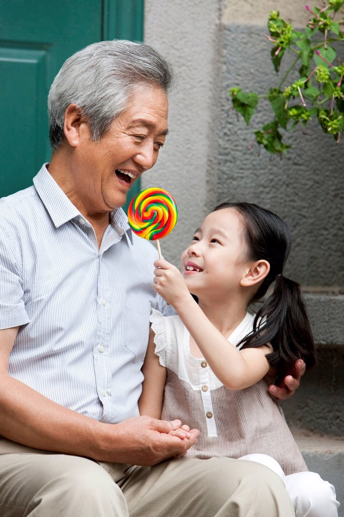 Stock Photo: 1839R-19097 Chinese Grandfather and Grandaughter with lollipop on front stoop