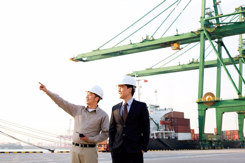 shipping industry worker showing a businessman around the port : Stock Photo