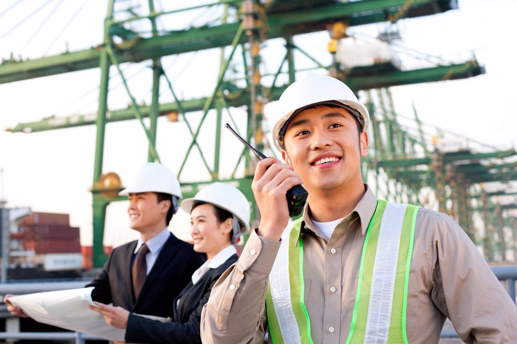 shipping industry worker using a walkie_talkie with businesspeople looking over blueprints in the background : Stock Photo