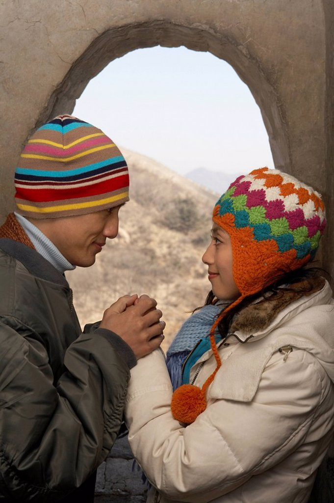 Stock Photo: 1839R-1930 Young Couple On The Great Wall Of China Smiling At Each Other And Holding Hands