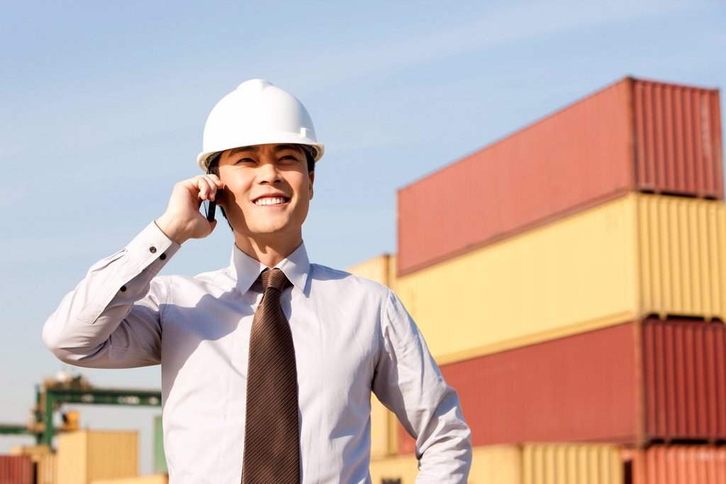 Stock Photo: 1839R-19941 businessman on his cellphone with cargo containers in the background