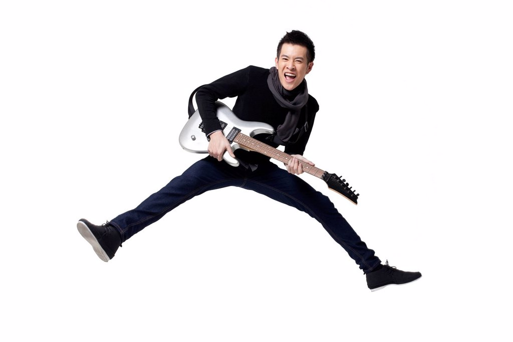 Stylish young man playing guitar : Stock Photo