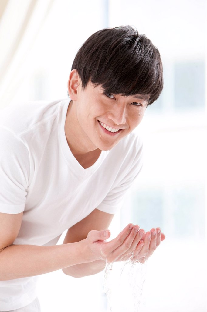 Stock Photo: 1839R-20135 Young man washing face