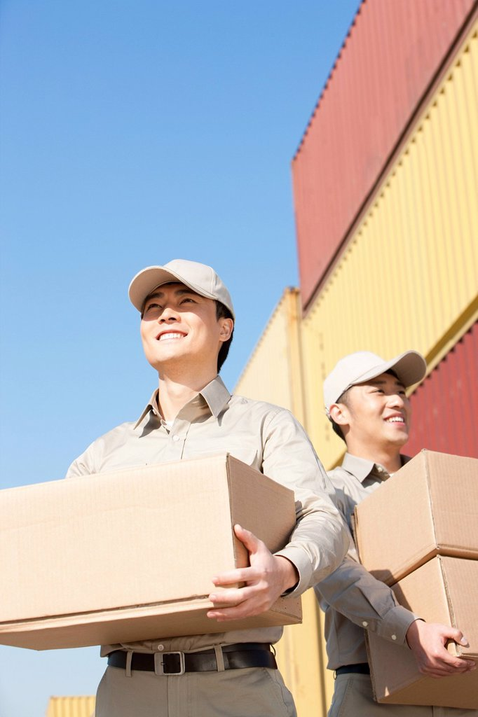 shipping industry workers carrying cardboard boxes : Stock Photo