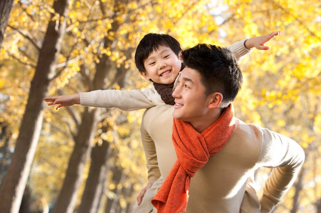 Father and son with arms outstretched and surrounded by Autumn trees : Stock Photo