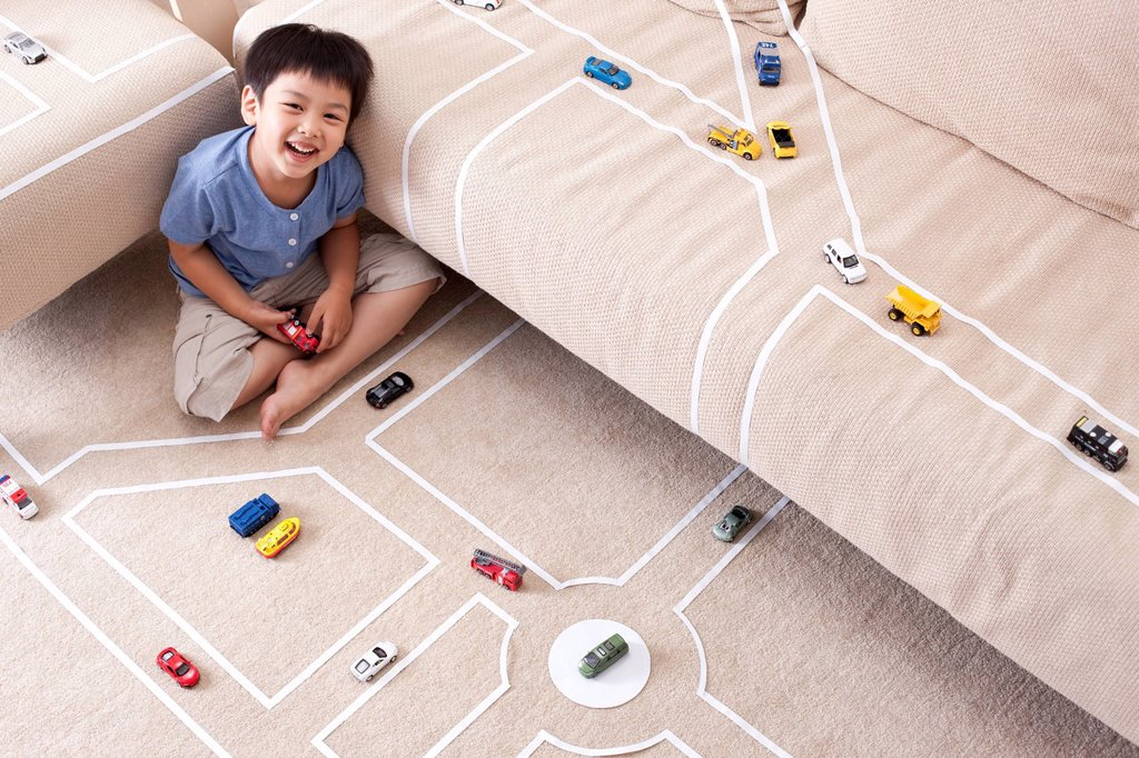Stock Photo: 1839R-20940 Boy playing toy car at home