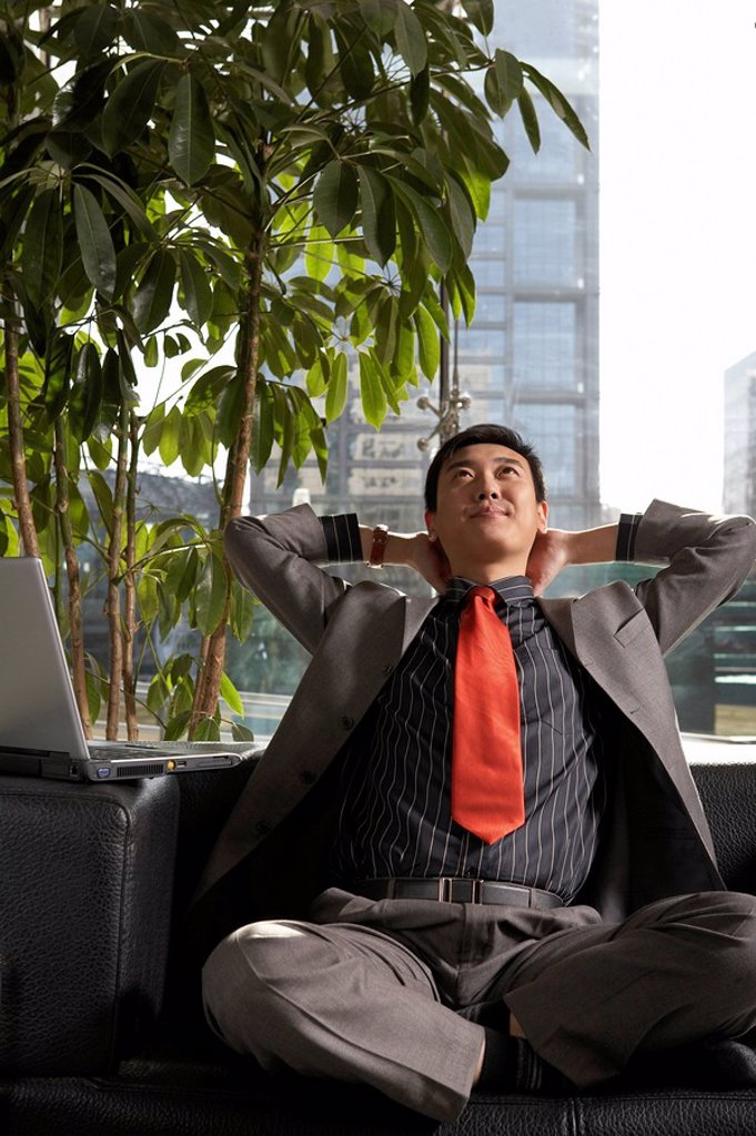 Stock Photo: 1839R-2134 Businessman Resting With Hands Behind His Head