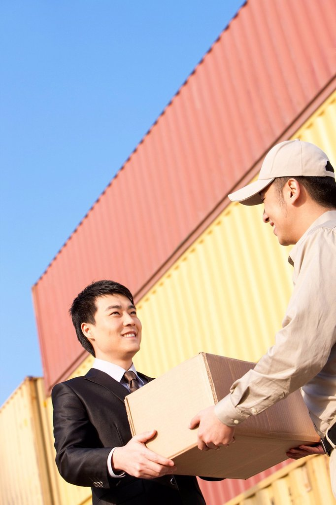 businessman and shipping industry worker giving and receiving a cardboard box : Stock Photo
