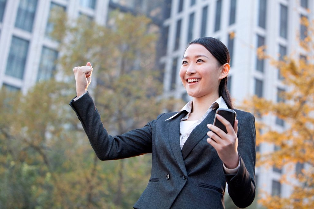 Businesswoman looking at her mobile phone and celebrating : Stock Photo
