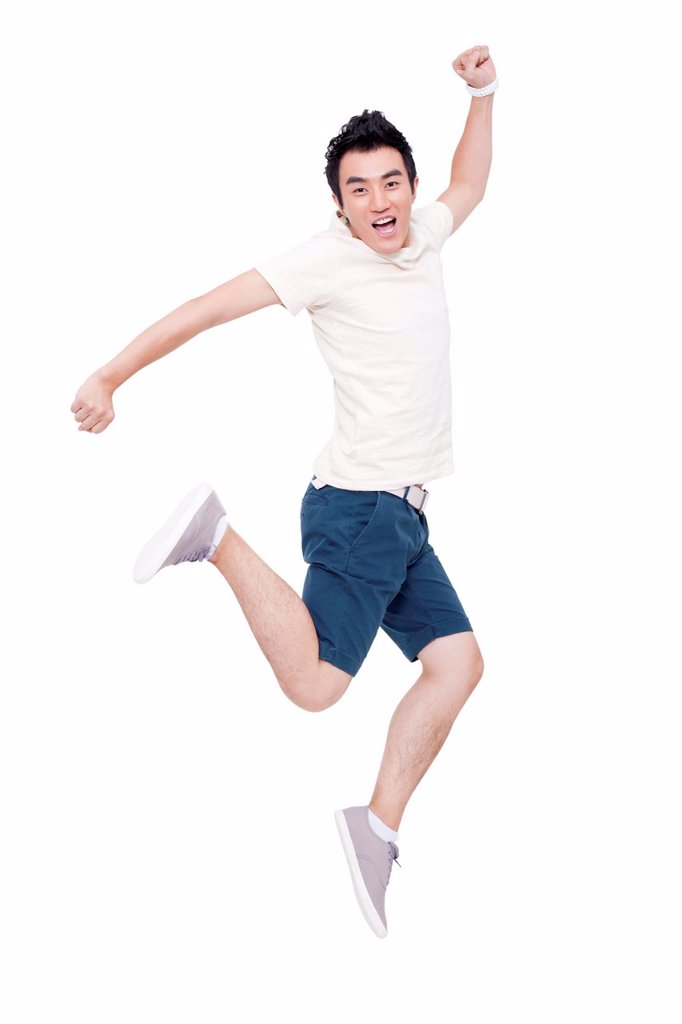 Cheerful young man jumping : Stock Photo