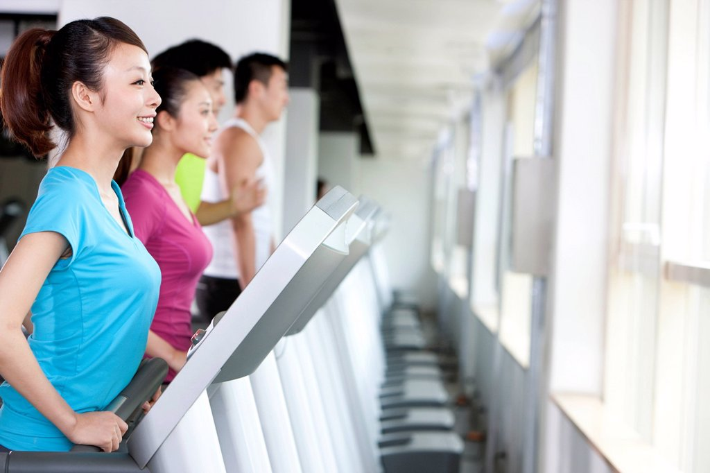 Four People Running on Treadmills : Stock Photo