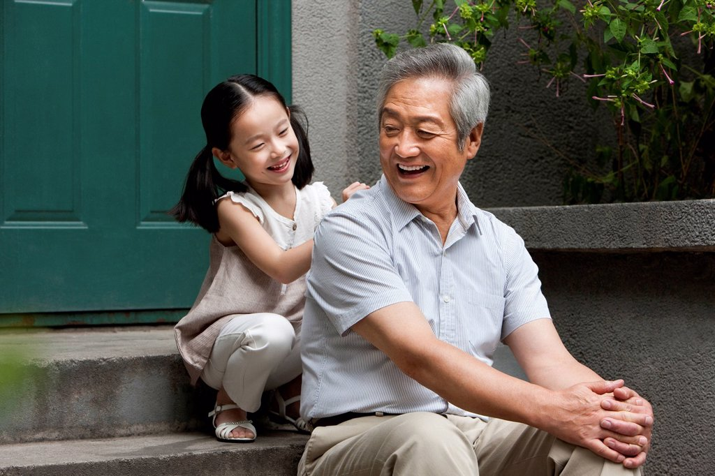 Stock Photo: 1839R-22116 Chinese Grandfather and Grandaughter on front stoop