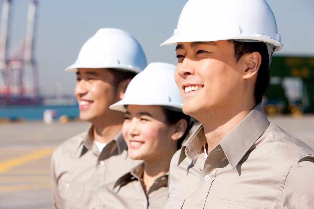 shipping industry workers looking in the distance : Stock Photo