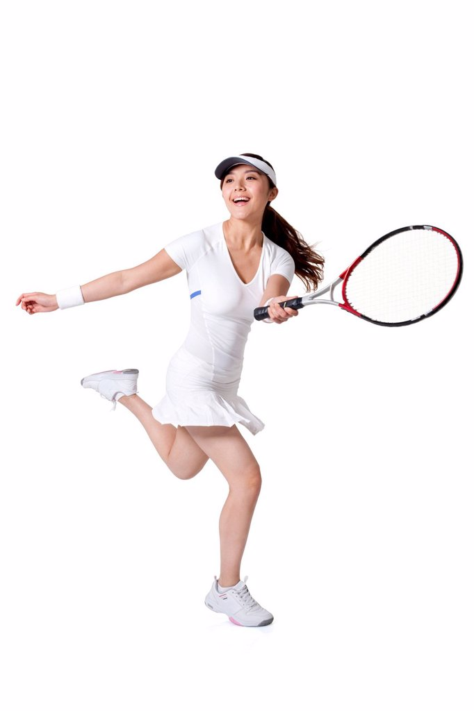 Young woman playing tennis : Stock Photo