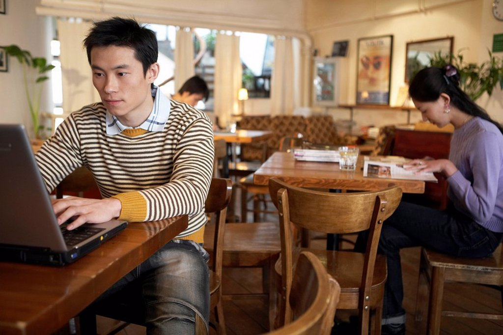 Young Man Sitting In Cafe On Laptop Computer : Stock Photo