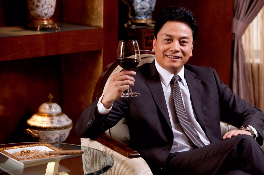 Stock Photo: 1839R-22446 Mature businessman enjoying wine in a luxurious room
