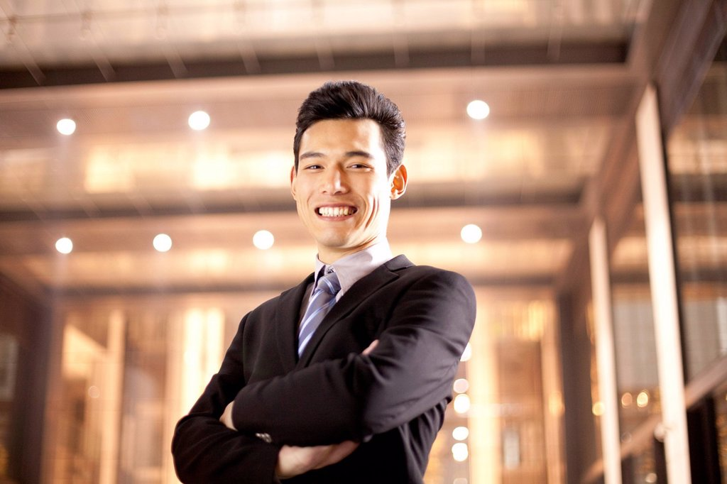A businessman outside an office building at night : Stock Photo