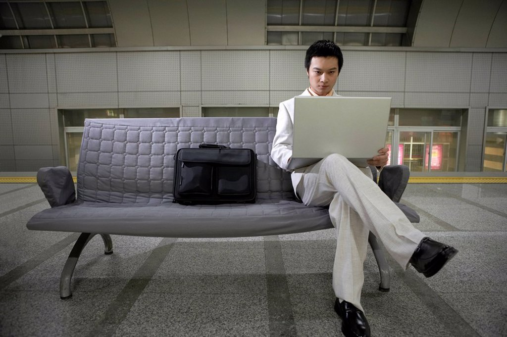 Man Using Laptop Sitting On Couch : Stock Photo