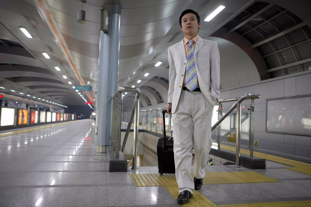 Stock Photo: 1839R-2393 Man Walking With Suitcase In Train Station