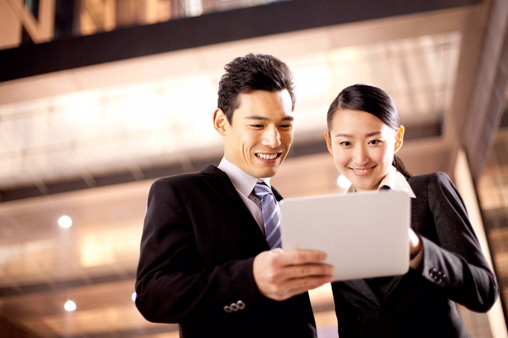Stock Photo: 1839R-24597 A businessman and businesswoman using a digital tablet outside an office building at night