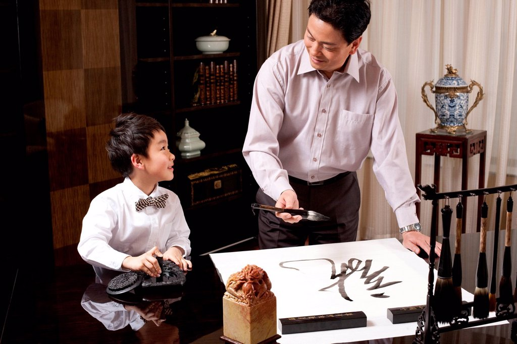 Grandpa and grandson practising Chinese calligraphy : Stock Photo