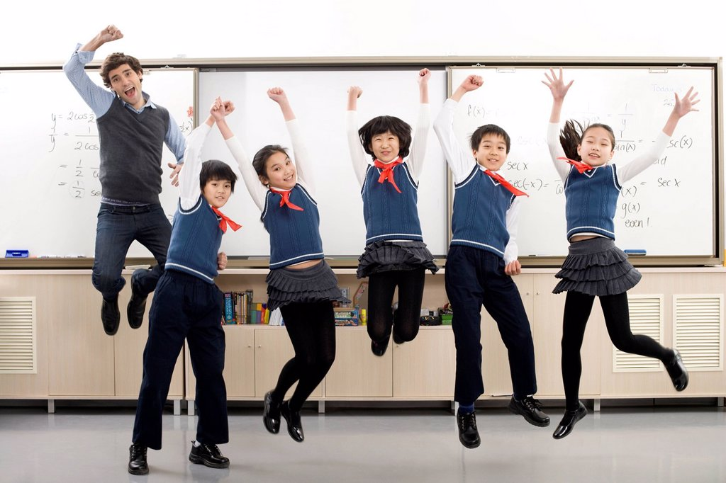 Teacher and students jumping in front of whiteboard : Stock Photo