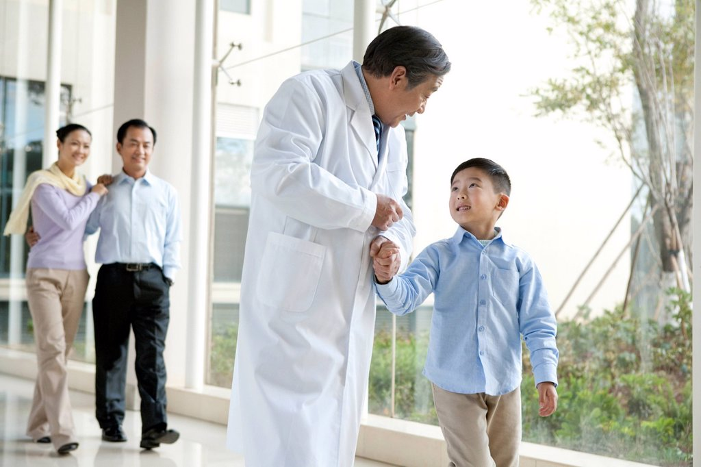 Stock Photo: 1839R-24977 Young Family Walks in a Hospital Corridor With a Doctor