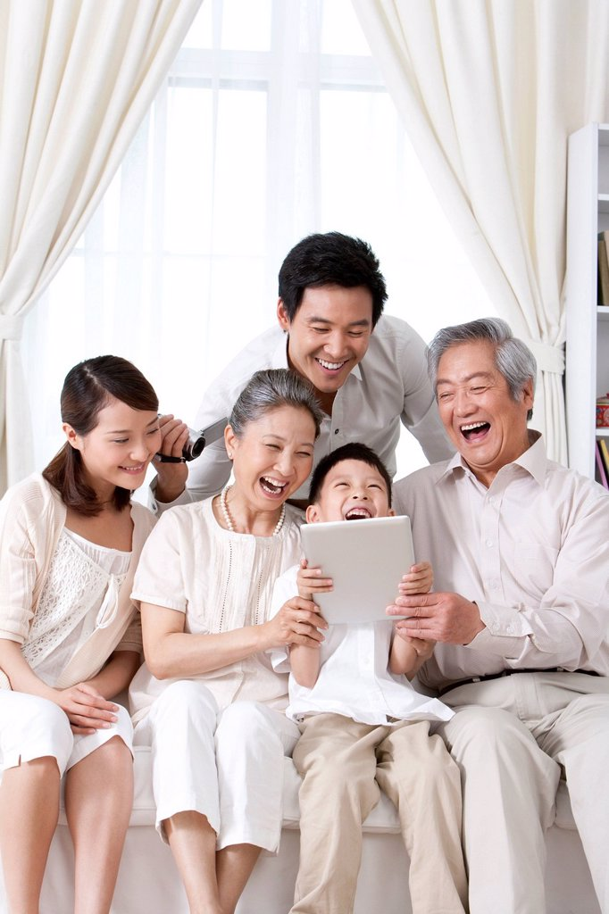 Happy Family Using an iPad together : Stock Photo