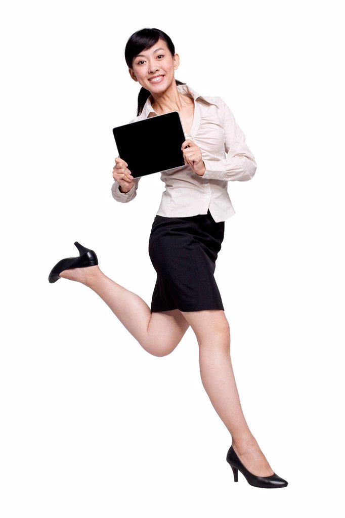Stock Photo: 1839R-25268 Businesswoman Jumping While Holding Digital Tablet