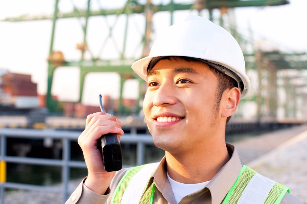 shipping industry worker using a walkie_talkie : Stock Photo