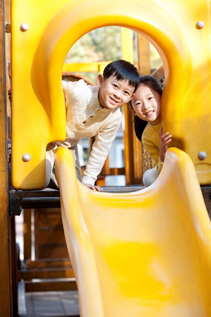 Stock Photo: 1839R-25382 Children playing on playground slide