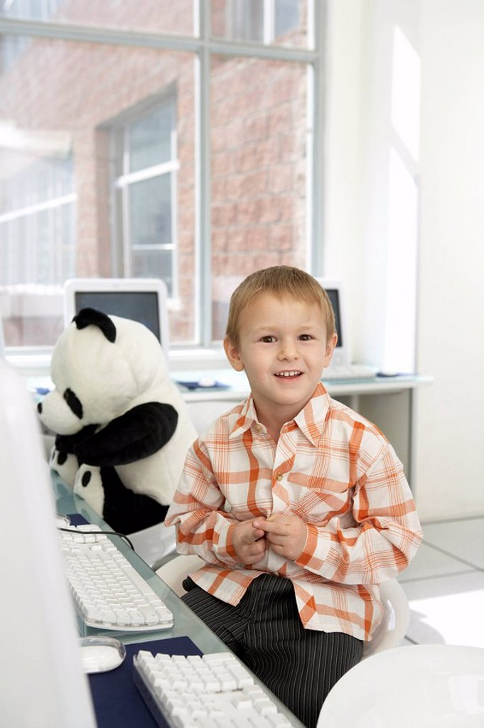 Stock Photo: 1839R-2551 Boy Sitting At Computer Desk