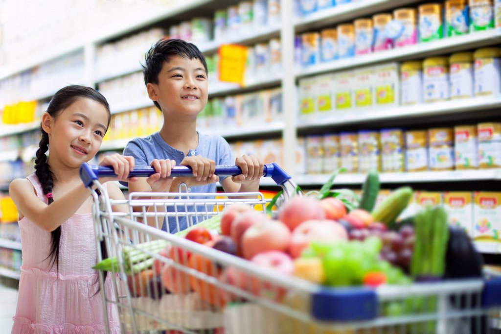 Children shopping in supermarket : Stock Photo