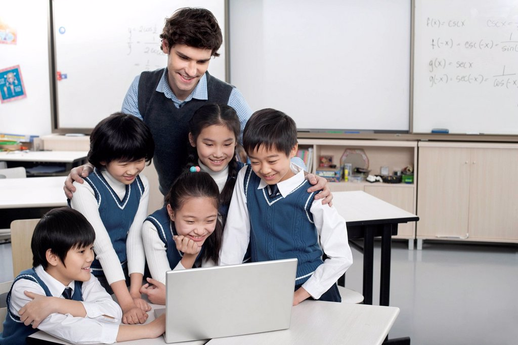 Students and teacher gathered around a computer in the classroom : Stock Photo