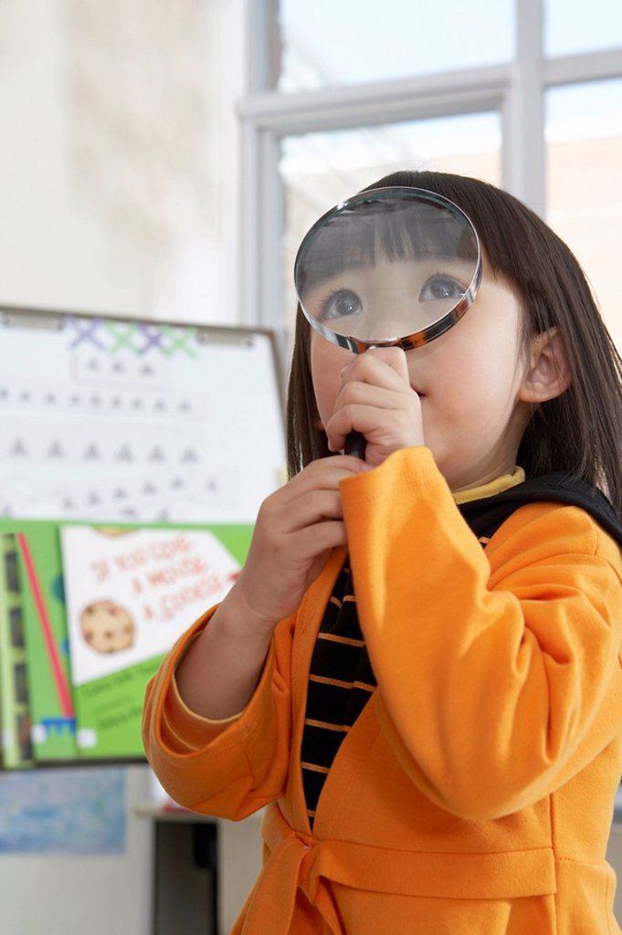 Stock Photo: 1839R-2591 Small Girl Looking Through Magnifying Glass