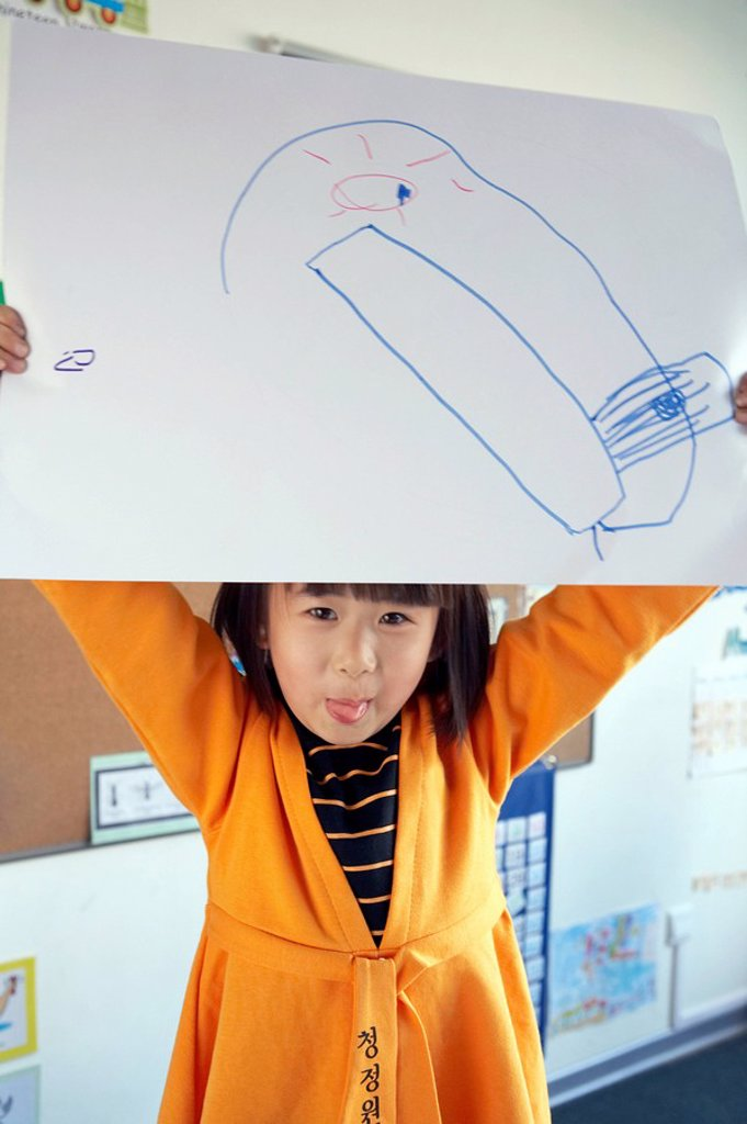 Girl With Tongue Poking Out Holding Up Drawing : Stock Photo