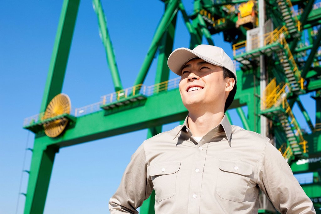 Male shipping industry worker with crane in the background : Stock Photo