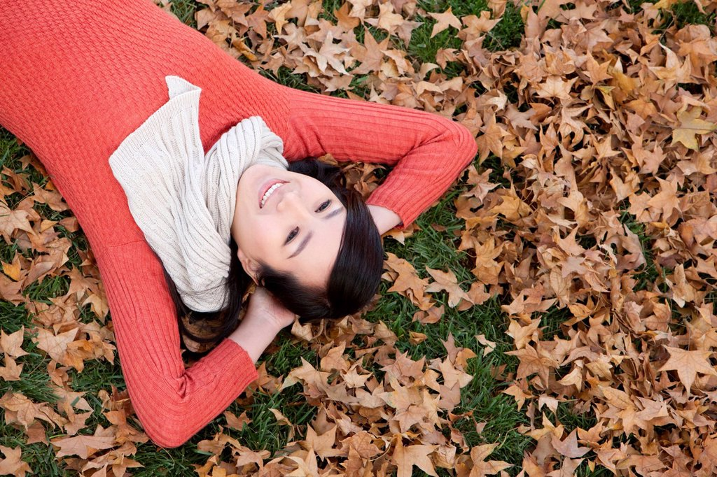 Stock Photo: 1839R-26158 Young woman lying on the grass surrounded by Autumn leaves