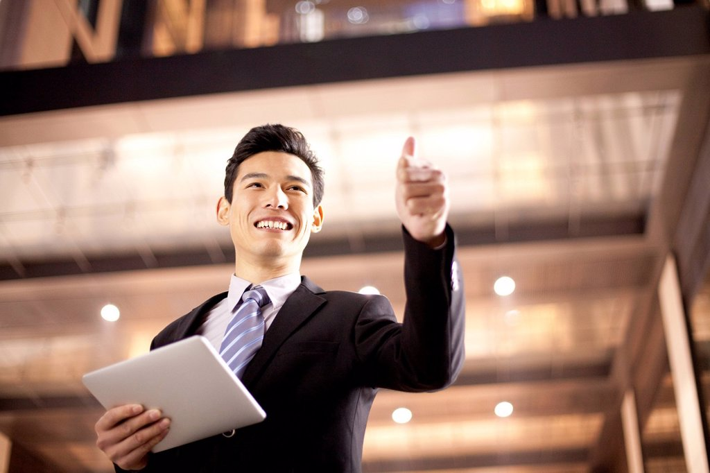 Stock Photo: 1839R-26174 A businessman using a digital tablet and giving a thumbs up outside an office building at night