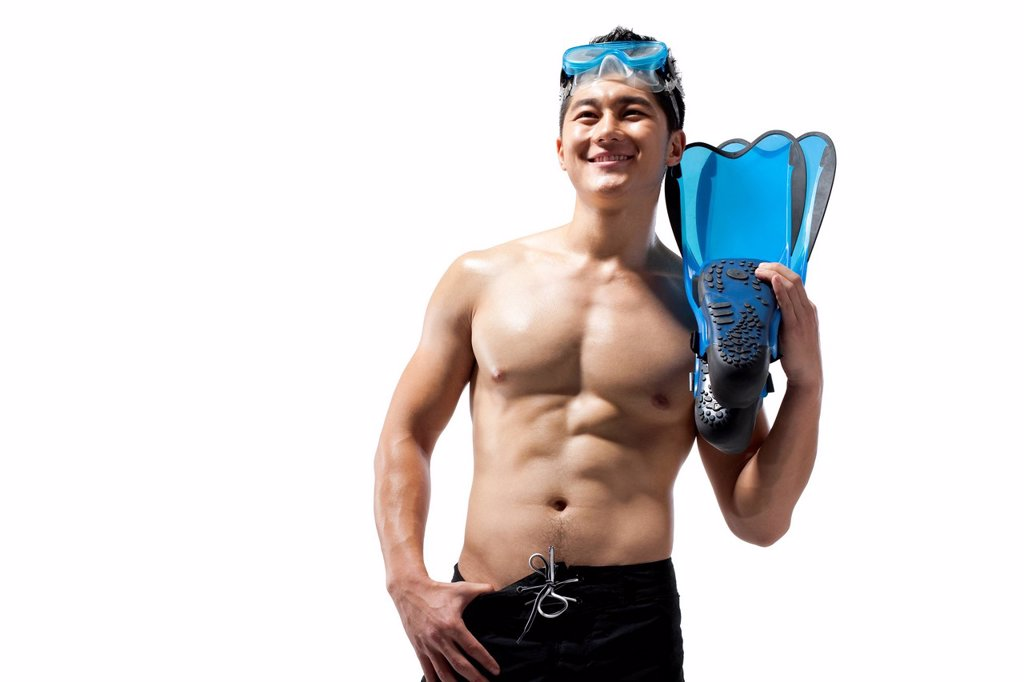 Shirtless muscular man holding swimming gear : Stock Photo