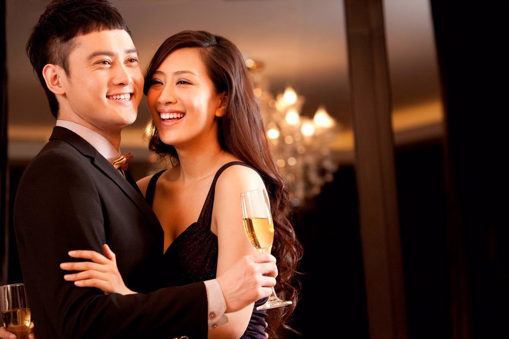 Stock Photo: 1839R-27181 Young couple having champagne in a luxurious room
