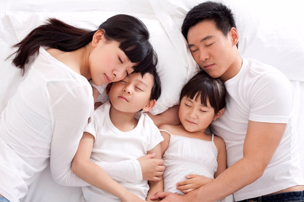 Happy family lying in bed : Stock Photo