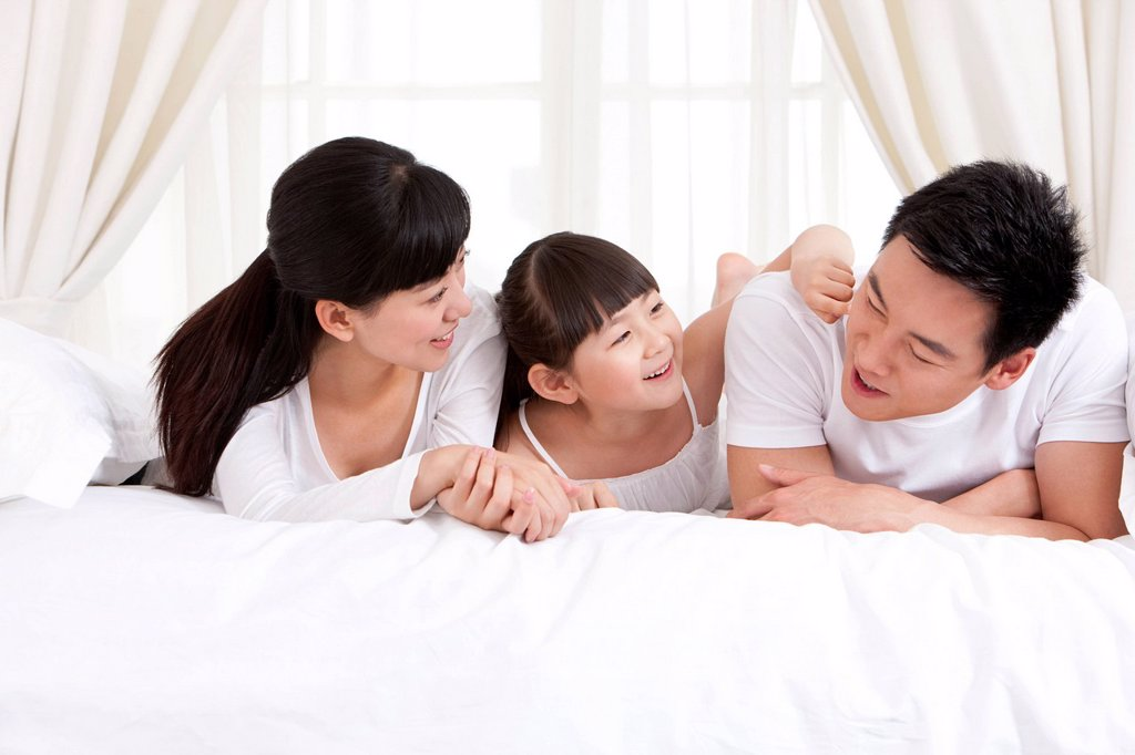 Stock Photo: 1839R-27218 Happy family lying in bed
