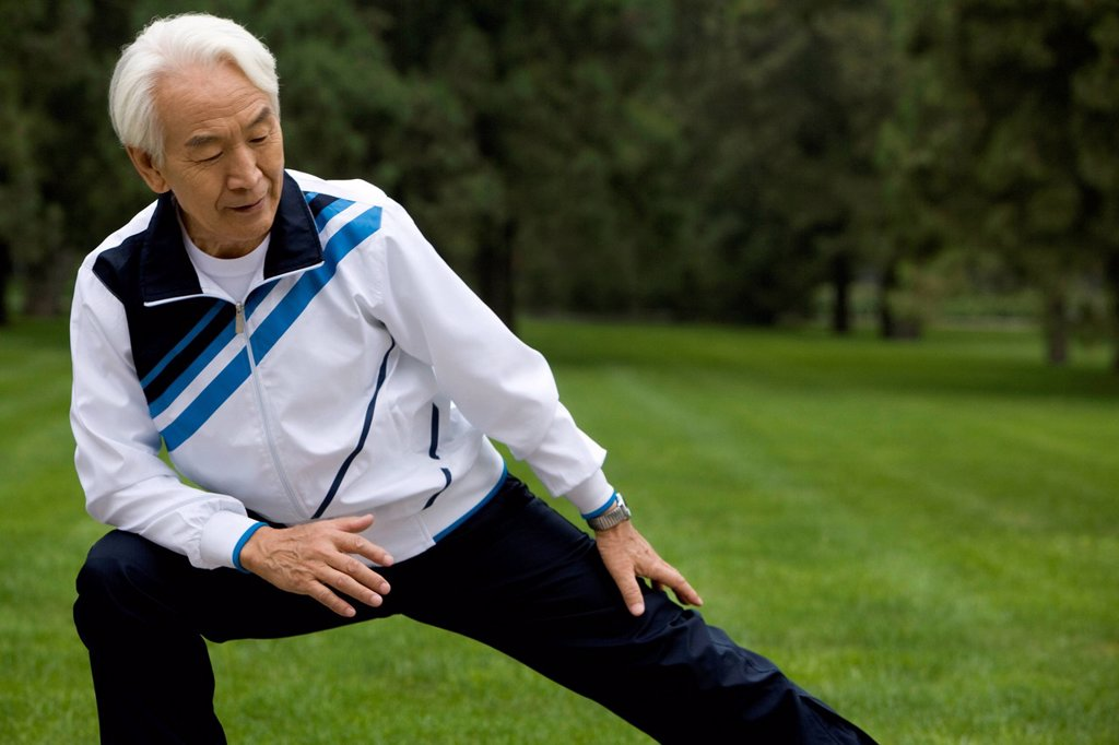 Stock Photo: 1839R-27335 Senior Man Stretching in a Park