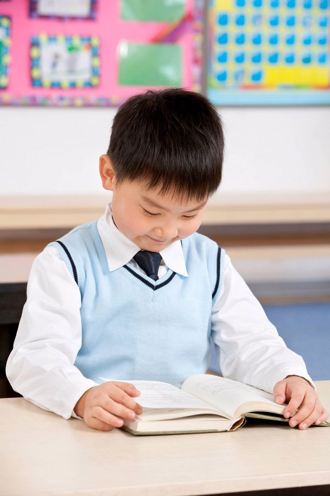 Young boy reading at his desk in a classroom : Stock Photo