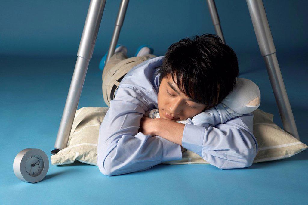 Stock Photo: 1839R-2796 Man Sleeping Under His Desk