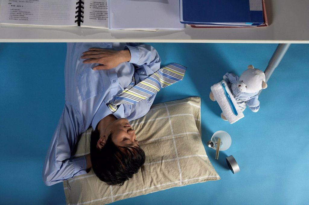 Stock Photo: 1839R-2798 Man Sleeping Under His Desk