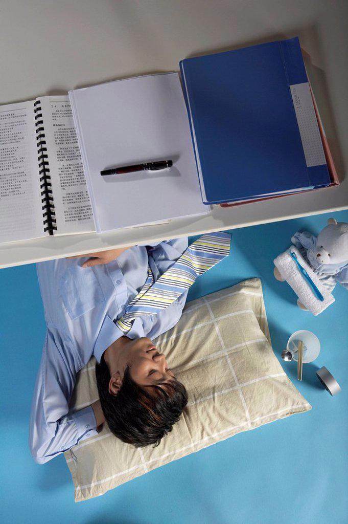 Stock Photo: 1839R-2799 Man Sleeping Under His Desk