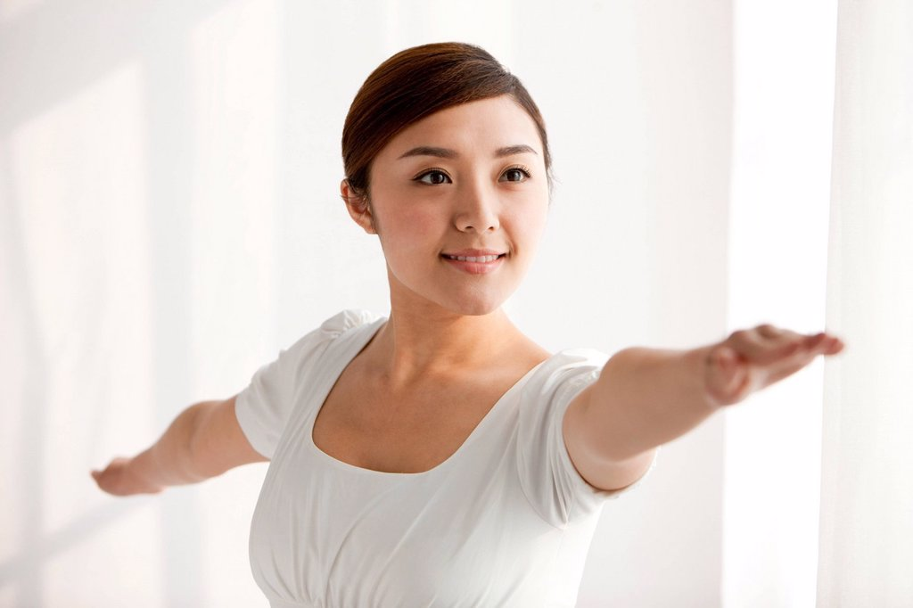 Stock Photo: 1839R-28620 Young woman practicing yoga with arms outstretched
